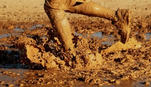 person running through mud at a mud run