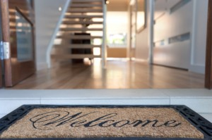 Close up of a welcome mat in front of an inviting house. Focus on foreground.