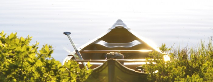 water and a canoe with a paddle