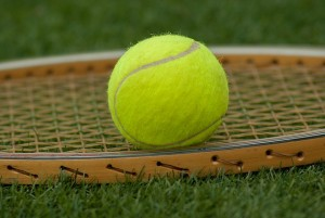 yellow tennis ball on a wooden racquet