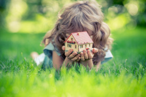 girl lying in the grass holding a yellow toy house with red roof