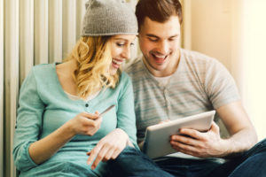 cheerful young couple looking at a tablet