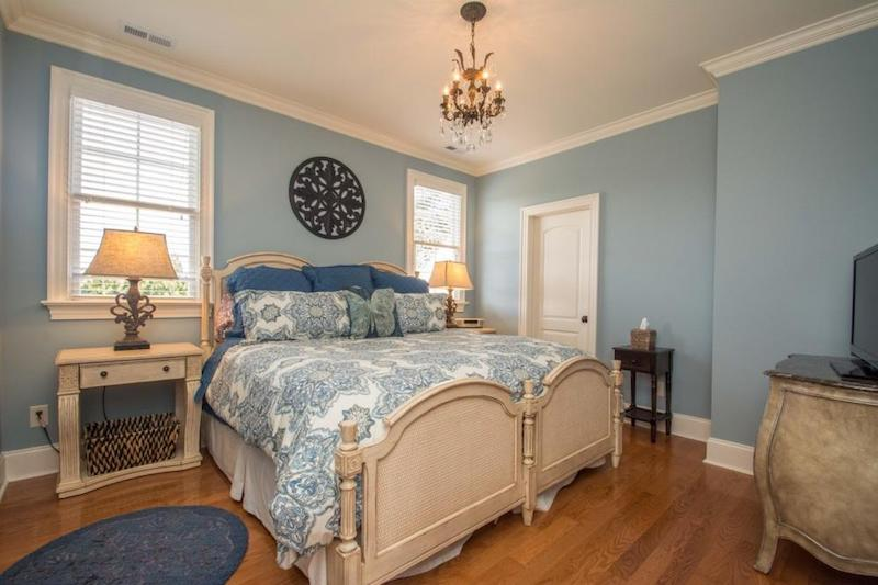 Clean staged bedroom with blue walls and hardwood floors