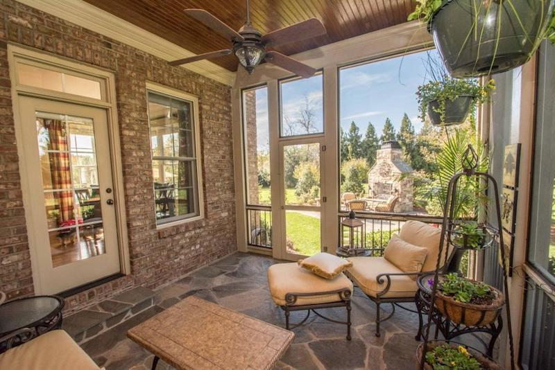 Screened in porch over looking backyard with fireplace with foliage
