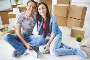 happy young couple sitting on the floor surrounded by moving boxes