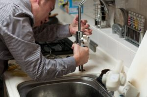 a man fixing a sink