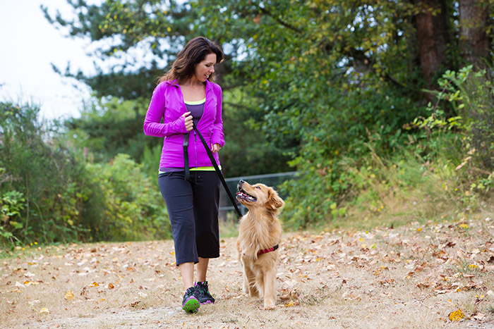 Woman walking with dog on a trail