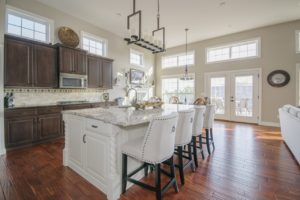 Luxury kitchen with big windows and white granite counters.
