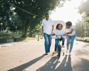 Two parents teaching their daughter how to ride a bike.