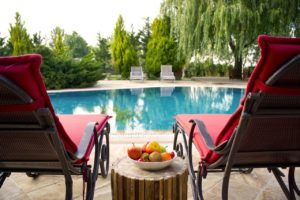 A luxurious outdoor pool with two red lounge charis.