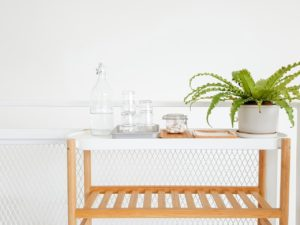 Small bar cart with glasses of water and a plant on the top in a white hallway.