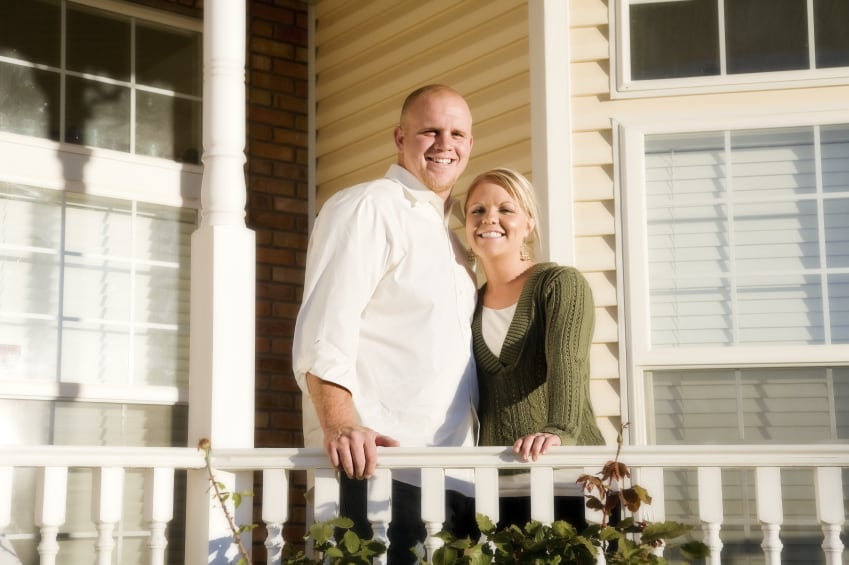 A married couple standing on the porch of their new home.