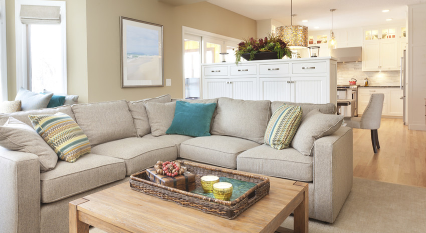 Spacious living room with beige sectional sofa and a coffee table.