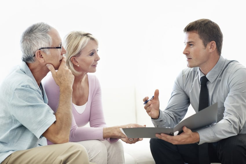 Elderly couple talking with a real estate agent.