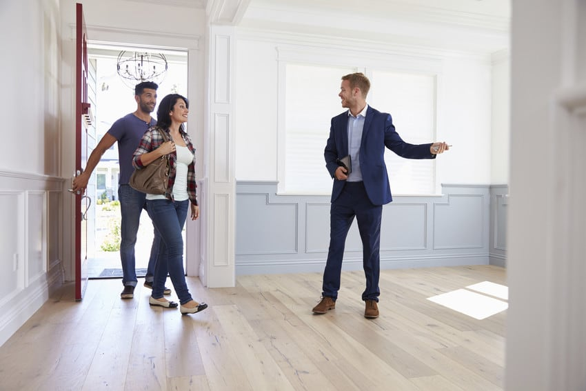 A couple touring a home for sale with a real estate agent.