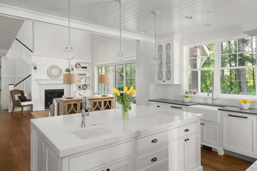 A gorgeous kitchen with hardwood floors and a white interior.