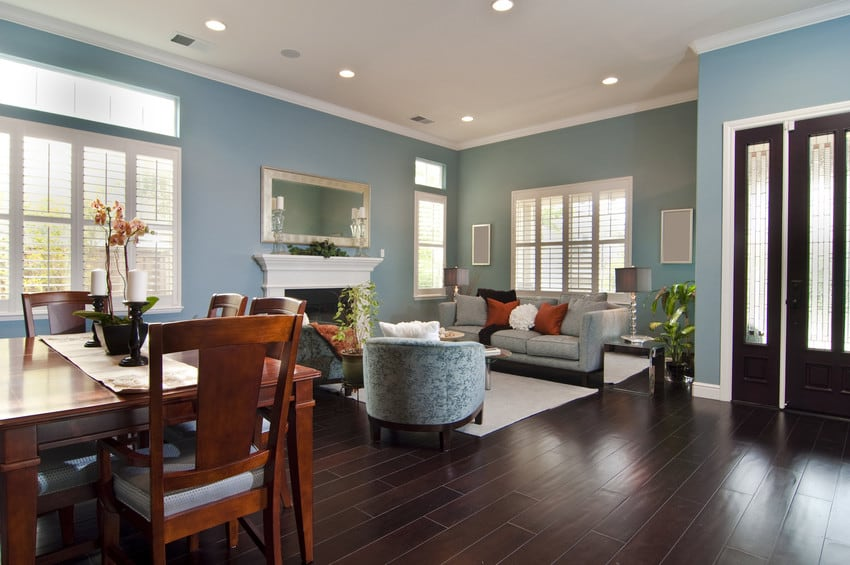 A living room with dark hardwood floors and blue walls.