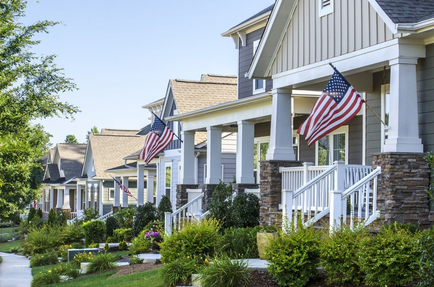 A row of suburban homes with American flags displayed outside.