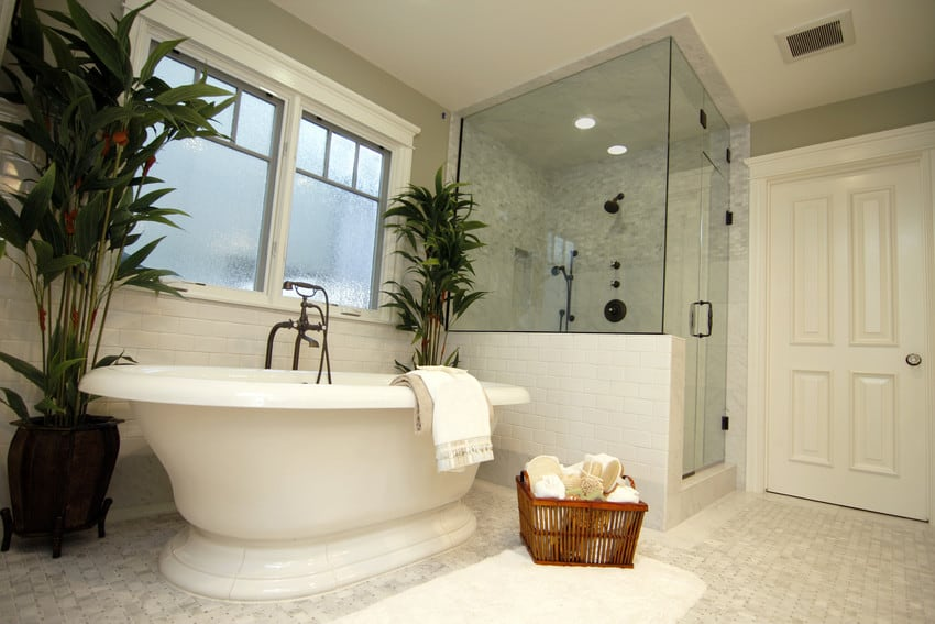 A huge white bathroom with a glass shower.