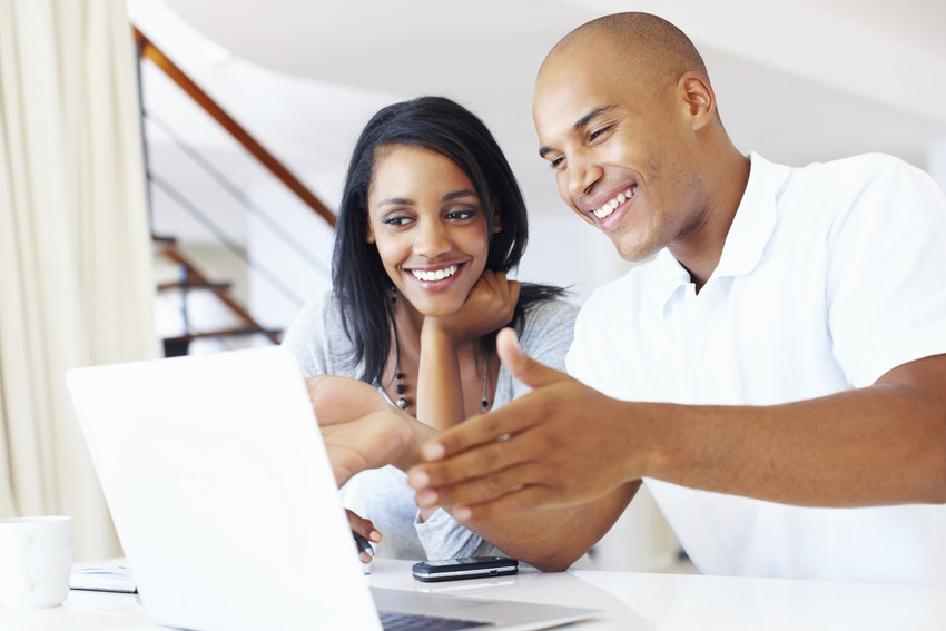 A couple sitting at a computer, smiling as they look at the results of their research.
