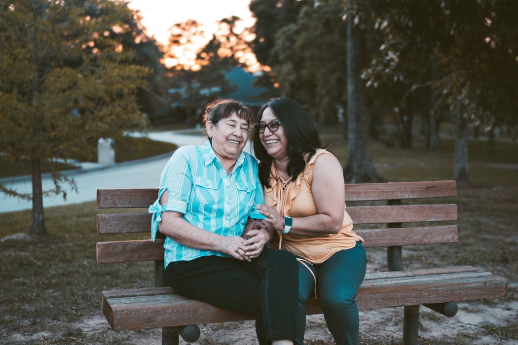 A daughter and mother sitting on a park bench.