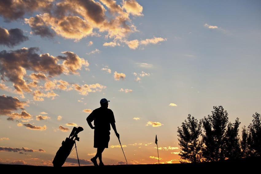A man standing on the golf course at sunset.