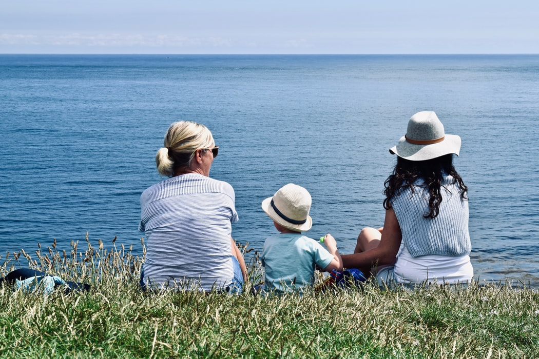 A grandmother, grandson, and daughter sitting by the water.