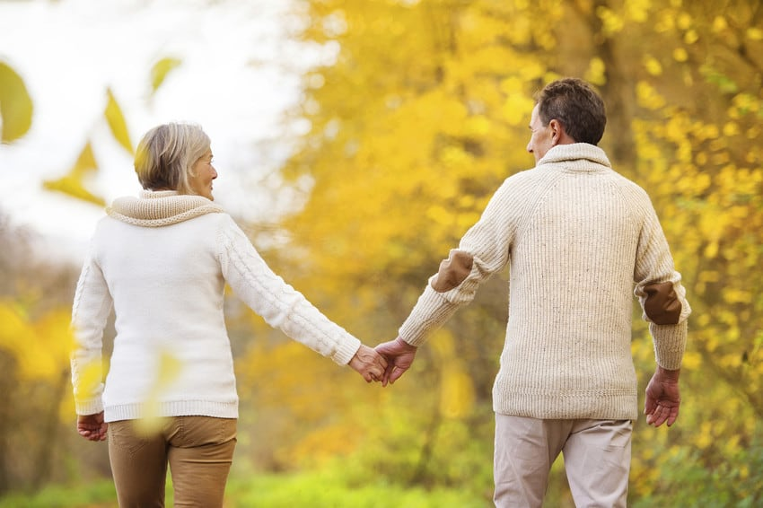 Two older adults holding hands.