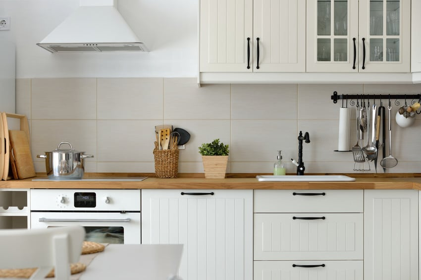 A simple kitchen with tile backsplash, wood countertops, and white paneled cabinets.