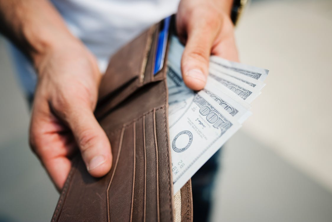 A man pulling money out of his wallet.
