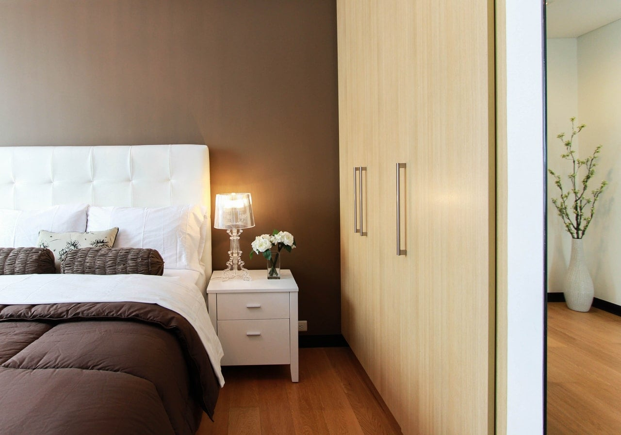 A large luxury bedroom with a white bed and wood closet.