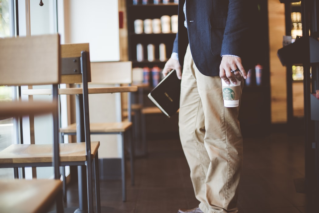 A man holding a Starbucks coffee.