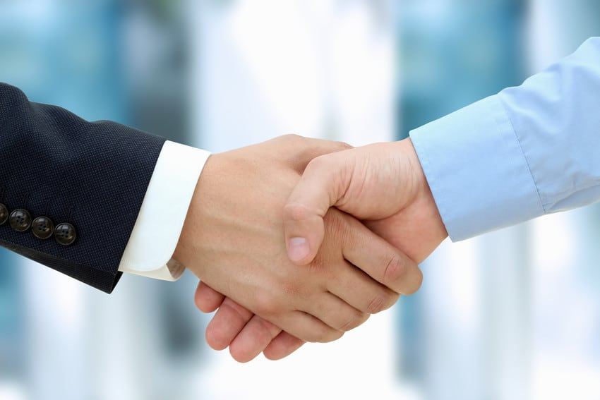 Two adults shaking hands.