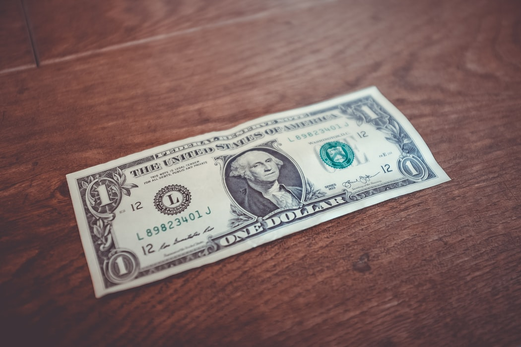 A single dollar bill sitting on a wooden surface.