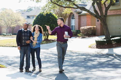 An agent leading buyers on a tour of homes during the late fall, a period of high buyer demand.