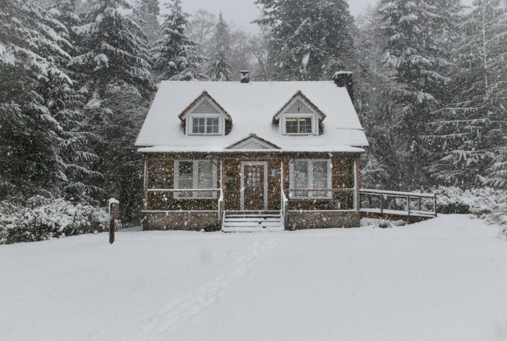 A home surrounded by snow in the winter.
