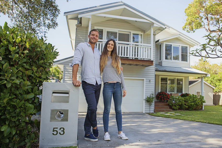 happy buyers outside a home