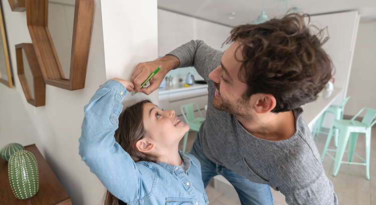 a father measuring his daughter