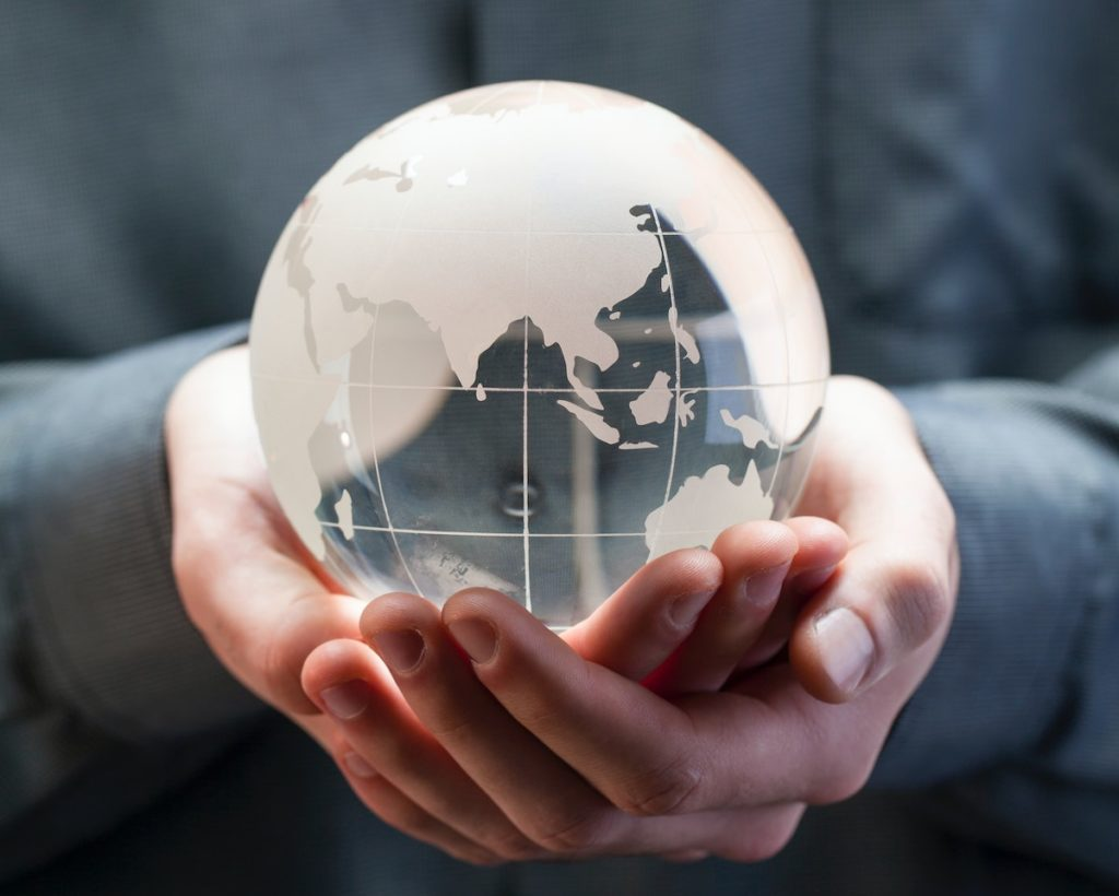 Person holding a glass globe with Luxe Places