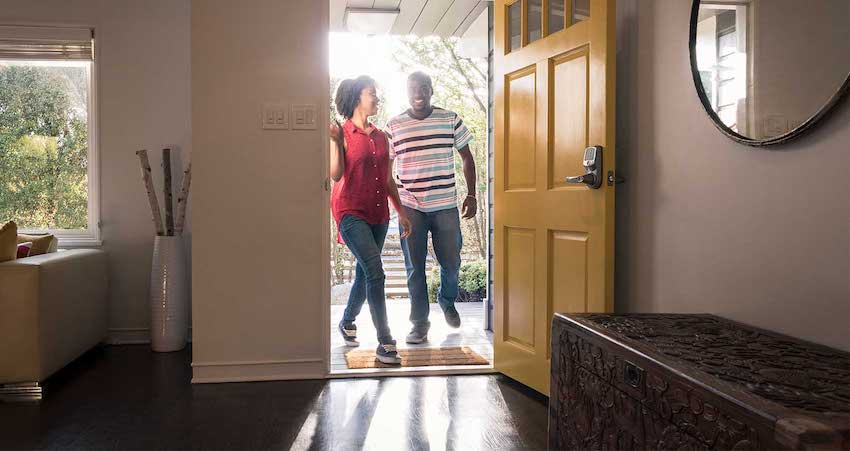 a man and a woman walking into their new home