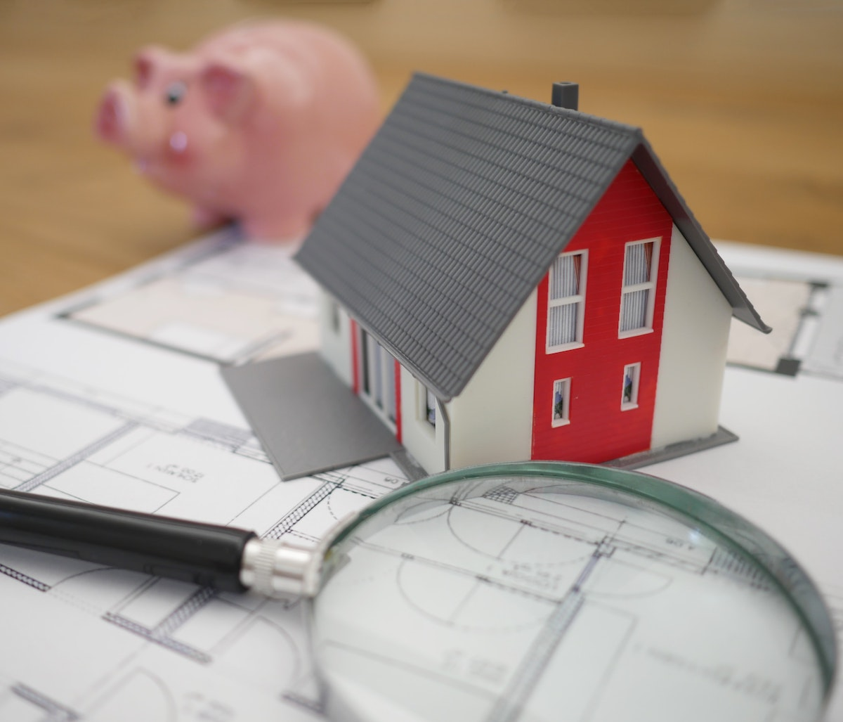 a house and a piggy bank on some papers
