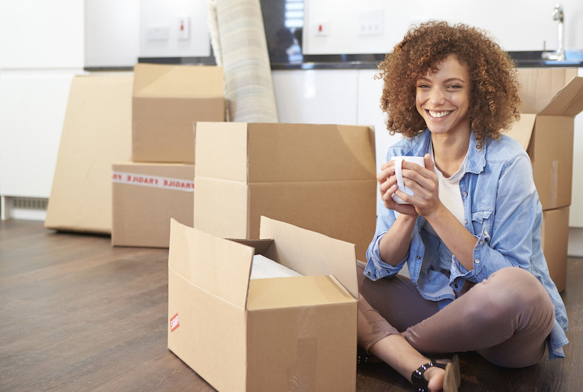 a woman smiling while packing moving boxes