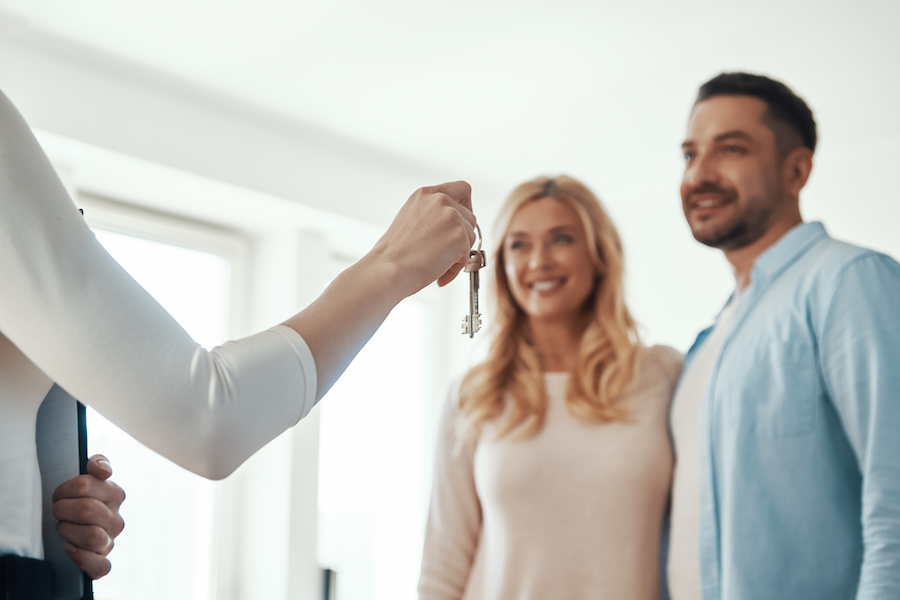 happy couple receiving keys to their new home